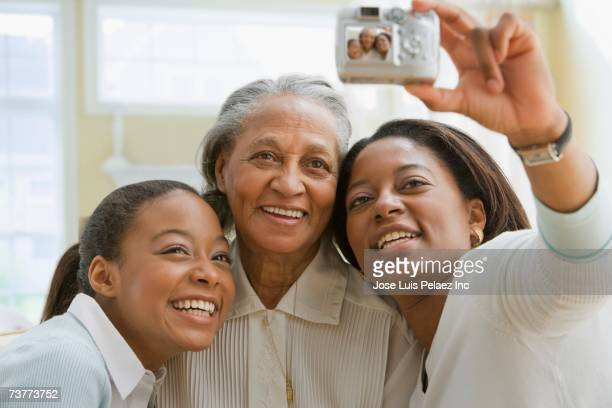 Three generations of African women smiling for photograph