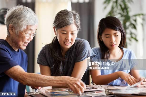Three generations of Asian women looking at photo album