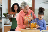 Three generations of Black women cooking in kitchen