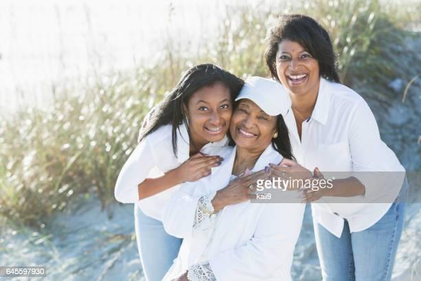 Three generations of black women posing on beach