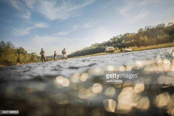 Three generations of Caucasian men fishing in river