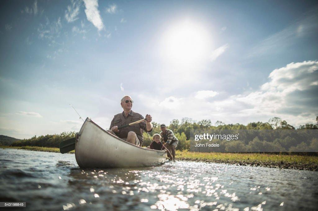 Three generations of Caucasian men paddling canoe in river