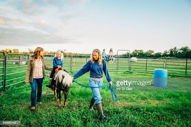 Three generations of Caucasian women walking miniature horse on farm