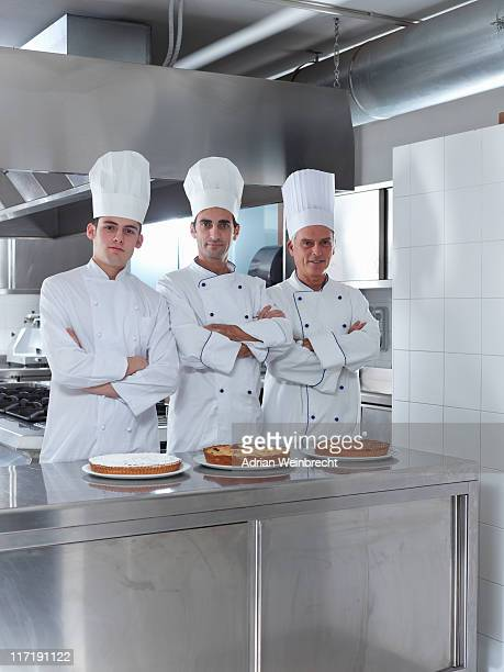 Three generations of chefs in restaurant kitchen with home made cake