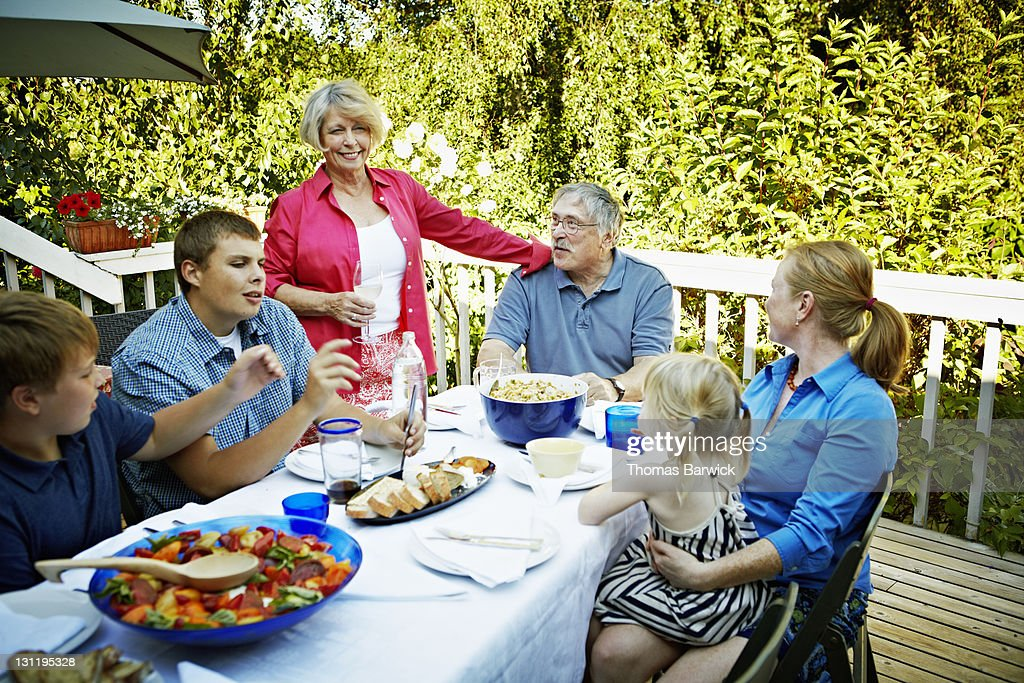 Three generations of family around table outside : Stock Photo