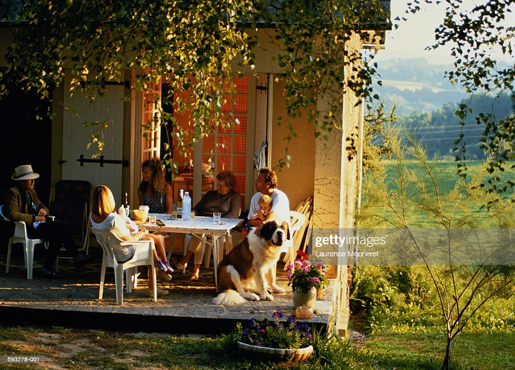 Three generations of family eating meal in front of house : Foto de stock