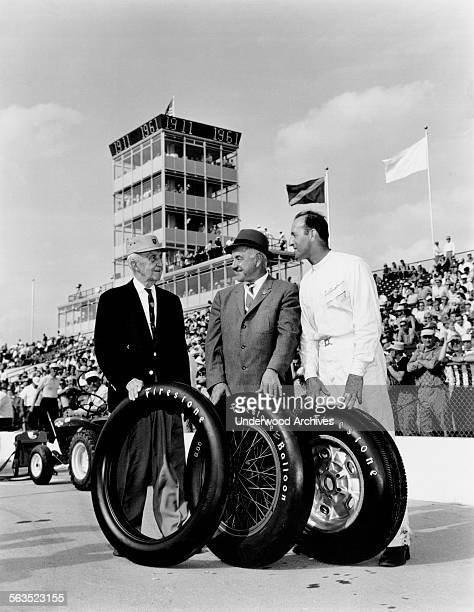 Three generations of Indy 500 race car drivers and the Firestone tires they drove on pose at the 50th anniversary of the race Indianapolis Indiana...