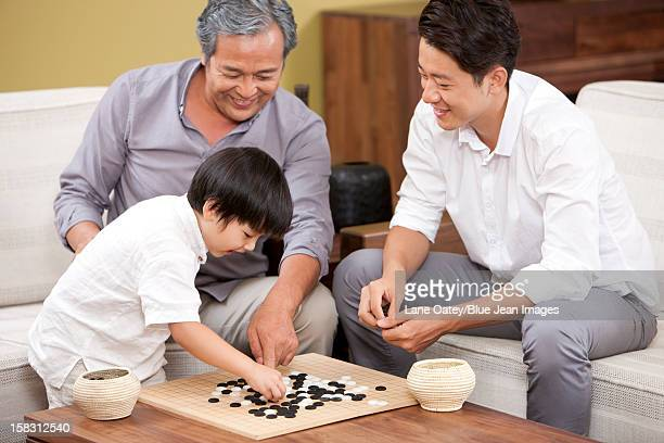 Three generations of men playing Chinese game of Go