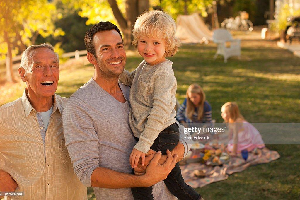 Three generations of men talking outdoors : Stock Photo
