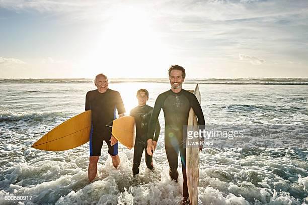 Three generations of surfers on beach