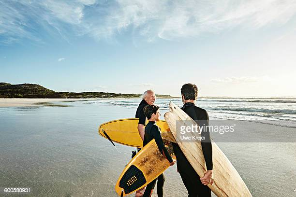 Three generations of surfers on beach