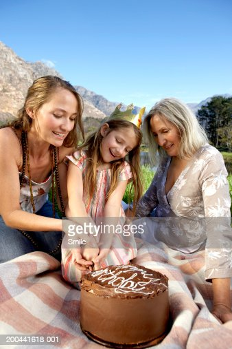 Three generations of women cutting birthday cake in field : Stock Photo
