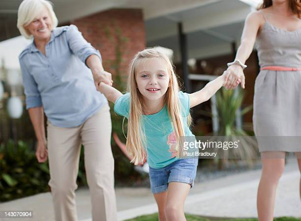 Three generations of women holding hands