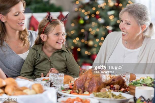 Drie generaties vrouwen lachen en bezoek tijdens het kerstdiner