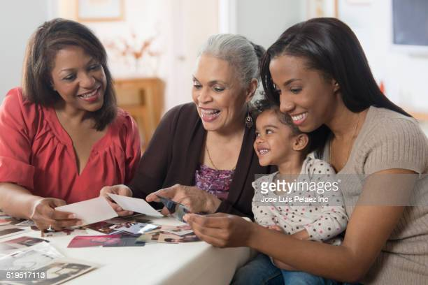 Three generations of women looking at photographs