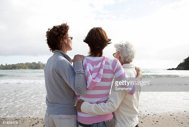 Three generations of women looking out to sea