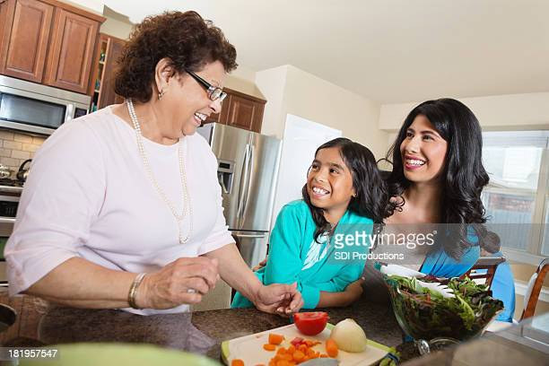 Three generations of women preparing dinner in family kitchen