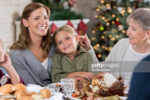 Drie generaties vrouwen zitten aan tafel