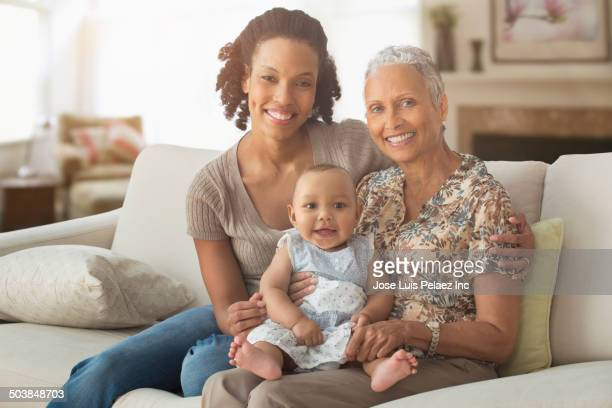 Three generations of women smiling on sofa