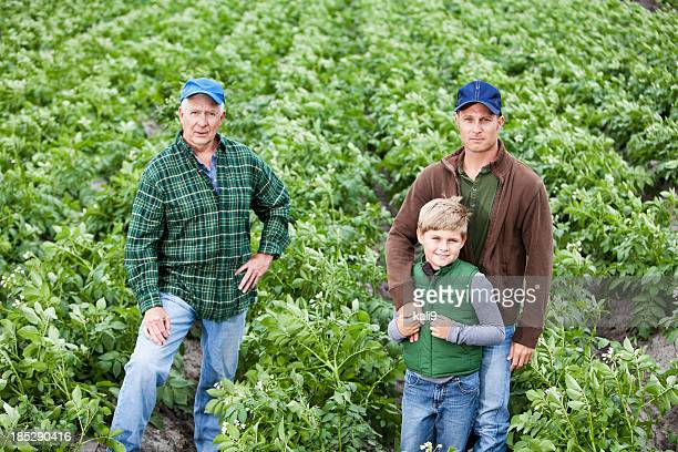 Three generations on the family farm, standing in potato field