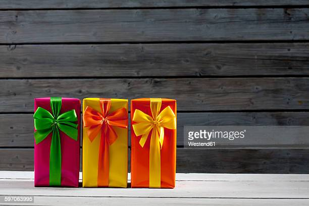 Three gift packages in front of wooden wall