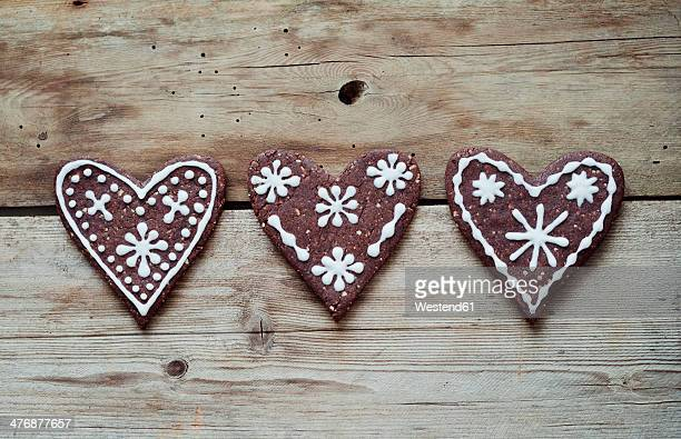 Three gingerbread hearts decorated with sugar icing on wooden table