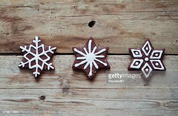 Three gingerbread stars decorated with sugar icing on wooden table