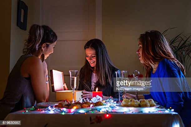 Three girl friends celebrating, opening gifts
