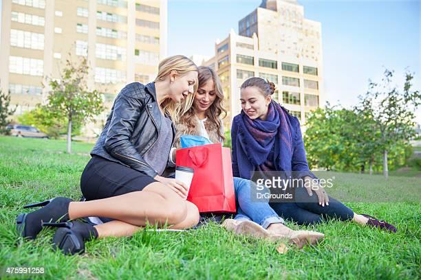 Três amigas verificar a sua purcheses em um Parque da cidade