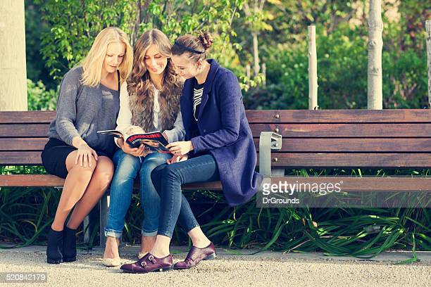 Three girlfriends reading magazine on bench outdoors