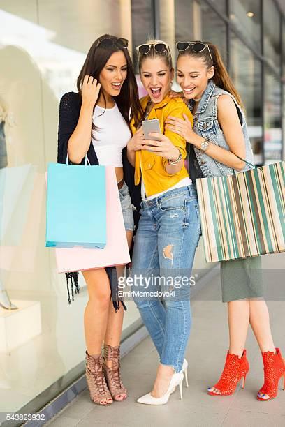 Três amigas surpreendido por o ver no telemóvel.