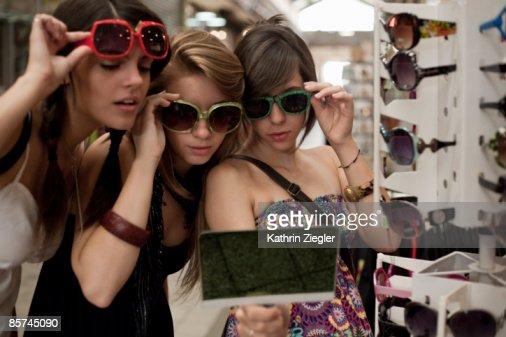 three girlfriends trying on sunglasses
