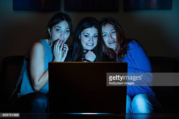 Three girlfriends, watchng something scary on laptop