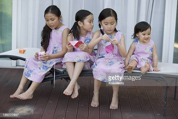 Three girls and a baby girl sitting together on a chaise longue