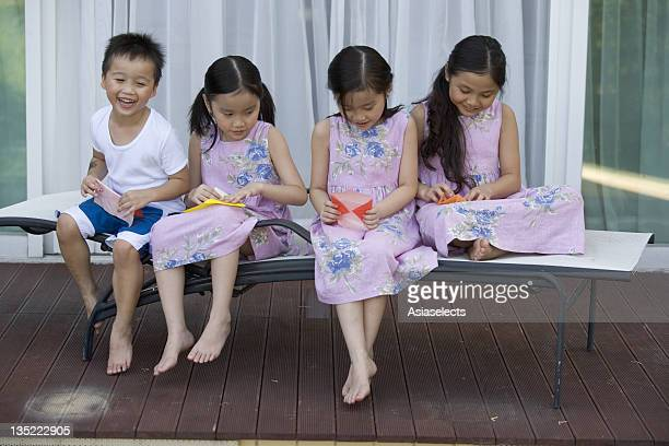 Three girls and a boy making paper airplanes