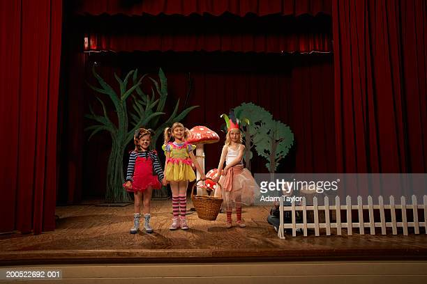 Three girls and boy (5-6) in fairy costumes performing on stage