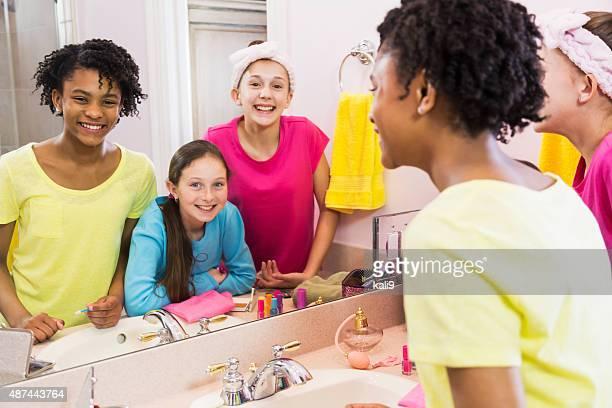 Three girls at sleepover looking into mirror in bathroom
