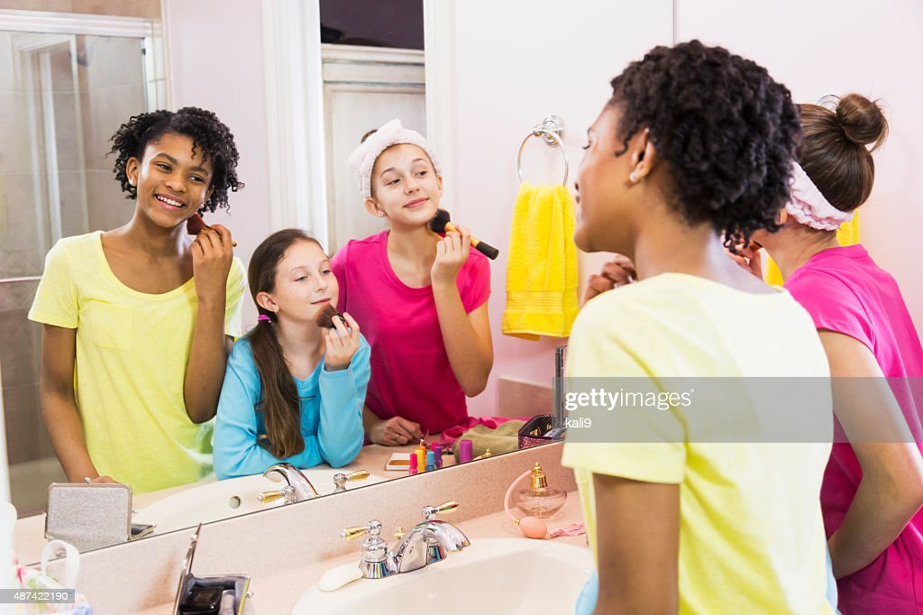 Three Girls At Sleepover Putting On Makeup In Bathroom : Stock Photo