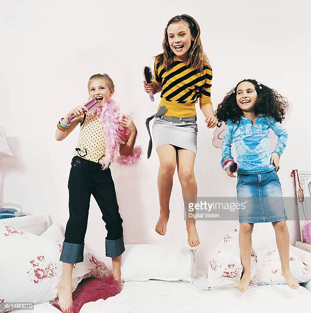 Three Girls Bouncing on a Bed and Singing Into Their Hairbrushes