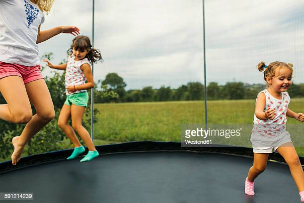 Three girls bouncing on trampoline