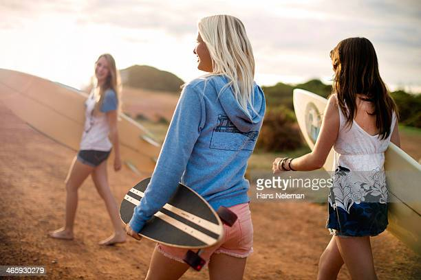 Three girls carrying longboards