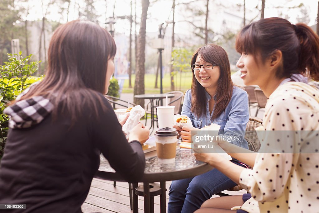 Three girls eating and talking : Stock Photo