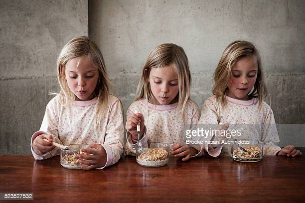 Three girls (7-9) eating cereal