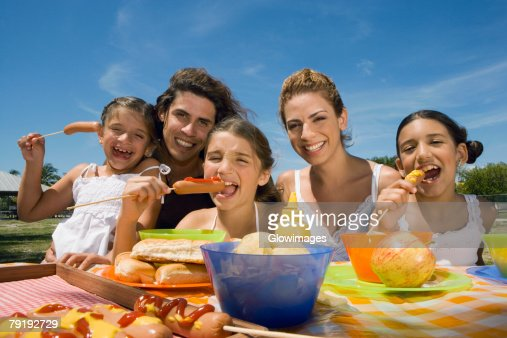 Three girls eating sausages with their parents in a picnic : Stock Photo