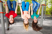 Three girls hanging upside-down on the brachiating bar at the sports ground during summer day with trees on background