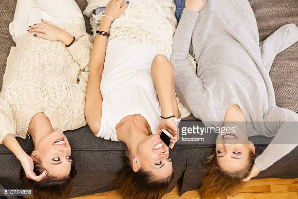 Three girls having fun, lying on bed