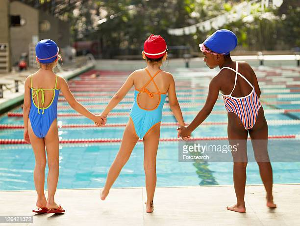 Three girls holding hands by swimming pool (rear view)