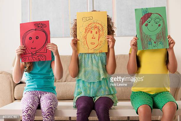 Three girls holding pictures over faces