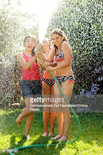 three girls in bathing suits playing with hose : Stock Photo