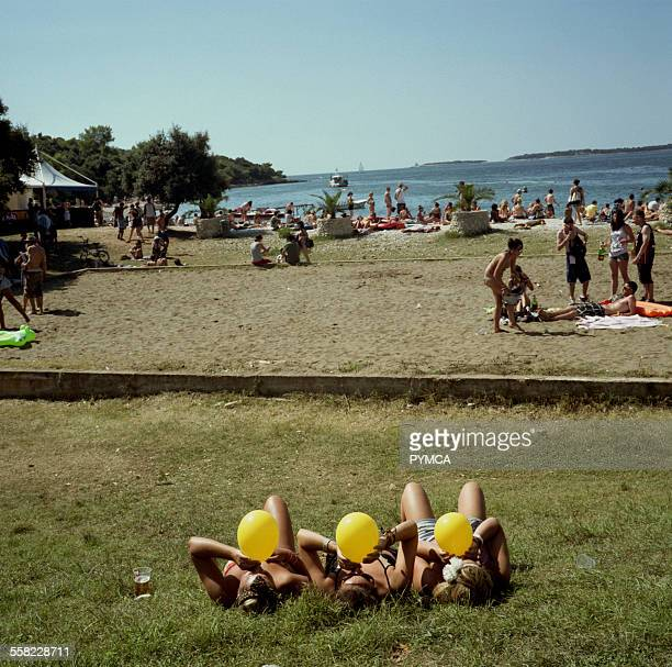 Three girls inhale laughing gas from yellow balloons sitting on a grassy bank next to the beach at Outlook Festival 2010 in Croatia